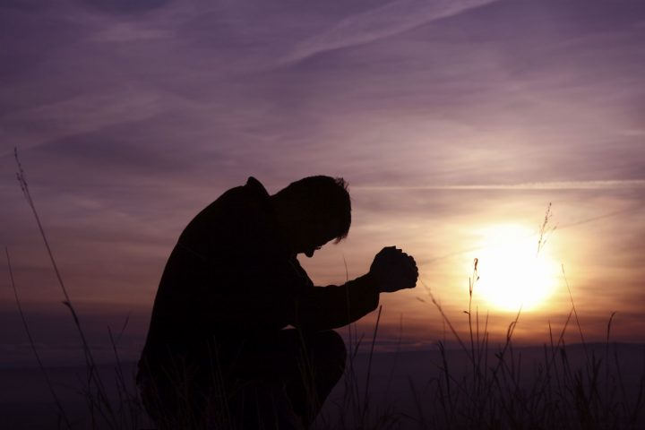 Man praying at sunset